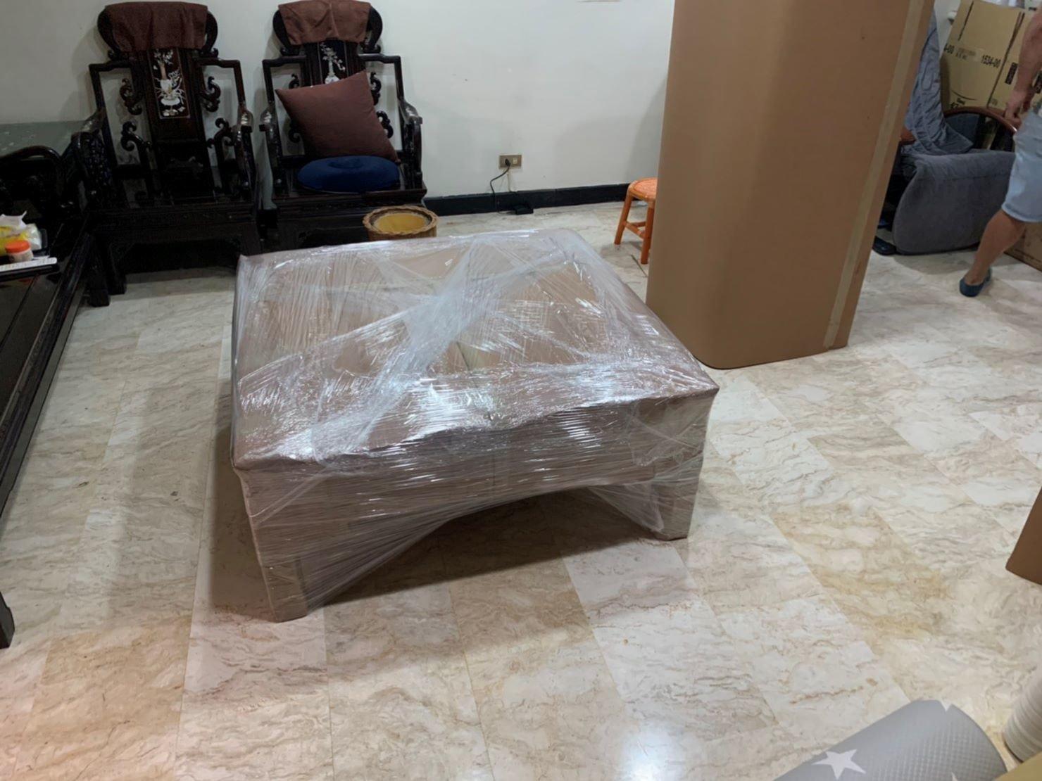 【榮福搬家公司】口碑第一、台北搬家:以膠膜、瓦楞紙將紅木雕刻玻璃桌做包裝防護,專業且細膩的包裝手法,給予家具最大的保護。